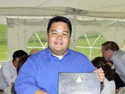 Mario Sengco holding his award at the 2002 WHOI Graduate Reception on McKee Ballfield.